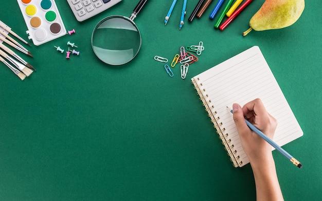 공책과 학용품이 있는 연필로 여자 손의 학생.
