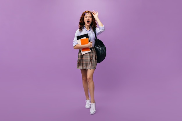 Student in plaid skirt holds notebook