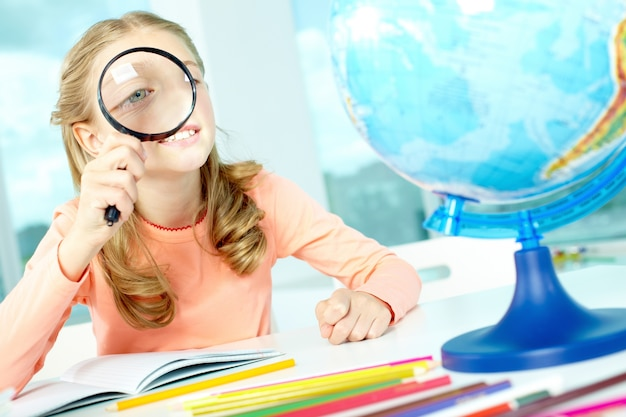 Student playing with a magnifying glass