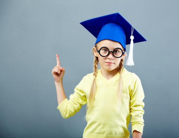 Student pointing up with graduation cap