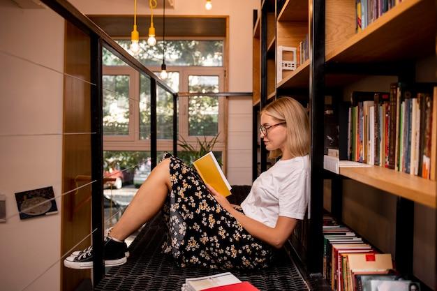 Студент читает книгу в библиотеке