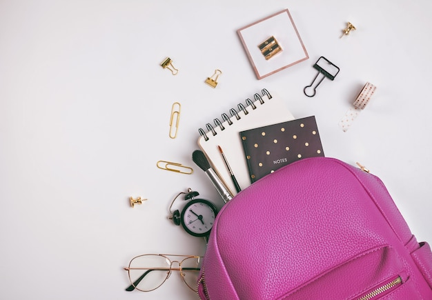 Student's backpack with different stationery and study supplies on the white