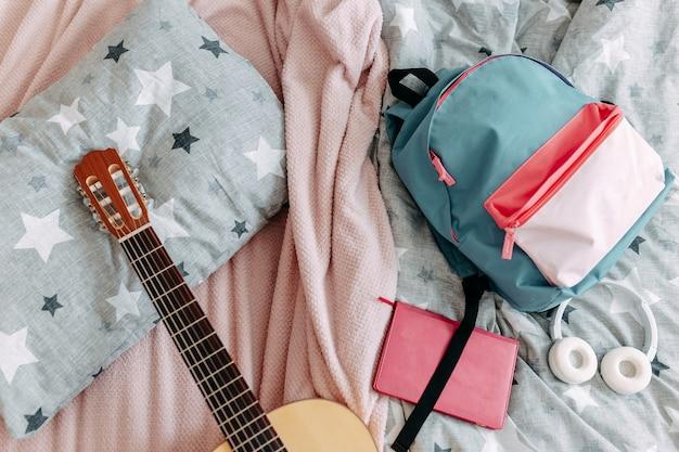 Студенческая комната после учебы. гитара, рюкзак, наушники и блокнот на кровати.
