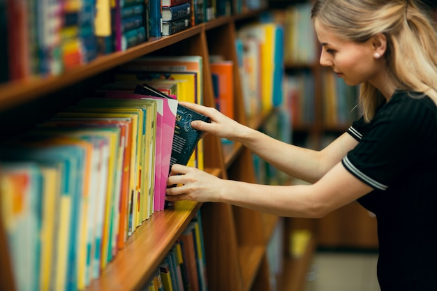 Student searching for books in a library