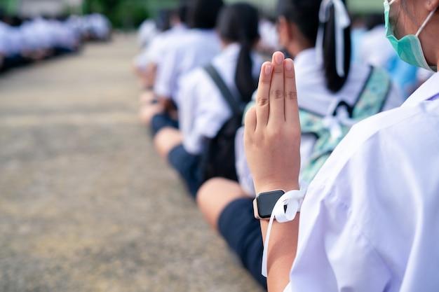 学校で3本の指の敬礼を示す学生