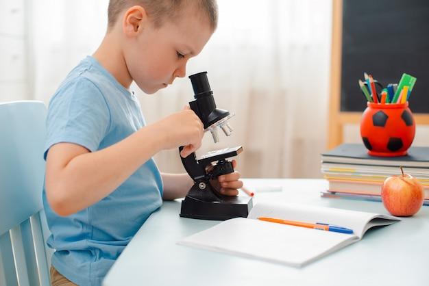 학생은 테이블에 앉아 교육 자료에 참여합니다. 학생은 현미경을 통해 보인다.