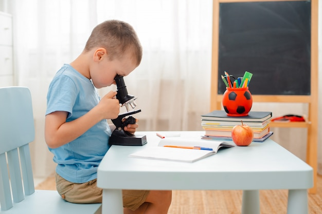 Student sits  table and engaged in educational material. schoolchild looks through a microscope.