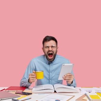 Студент сидит за столом с документами, держа чашку и планшет