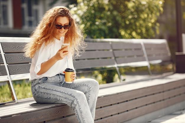 전화와 커피와 함께 도시에 앉아 학생