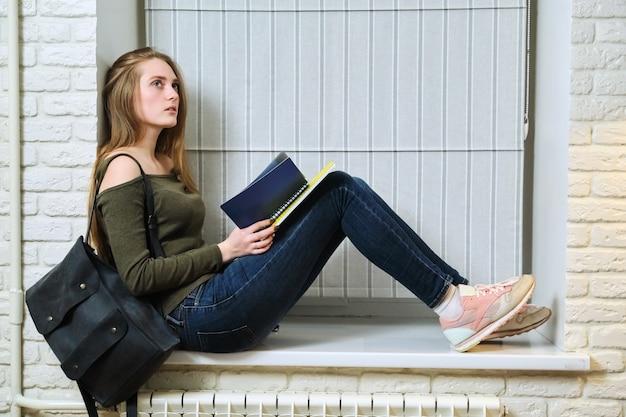 창턱에 앉아 공부, 노트북을 읽는 학생
