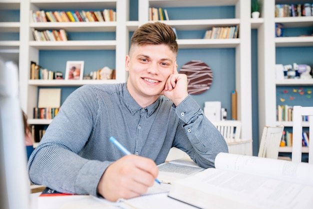 Student sitting with books and pen in library