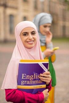 웃는 학생. 책을 들고 웃 고 아름 다운 검은 눈 무슬림 학생