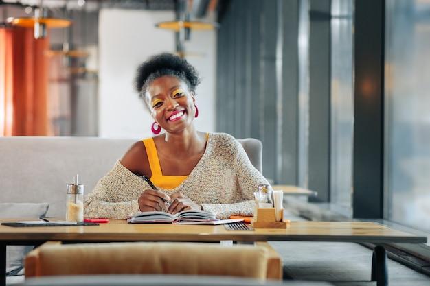 笑顔の学生 食堂でメモを取りながら微笑むスマートな留学生