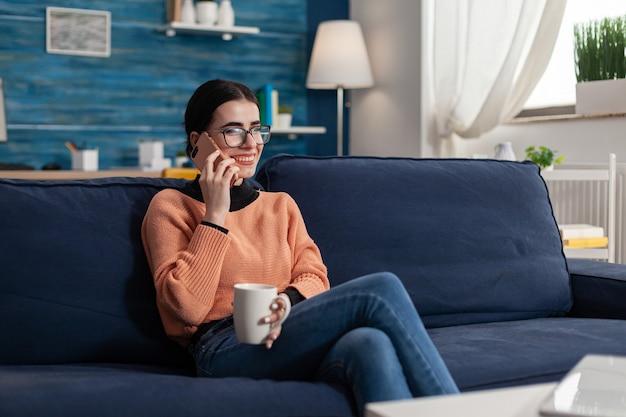 Студент улыбается во время разговора по телефону, держа чашку кофе, сидя на диване в гостиной. подросток консультируется со своей подругой по поводу совета по образу жизни во время карантина из-за коронавируса