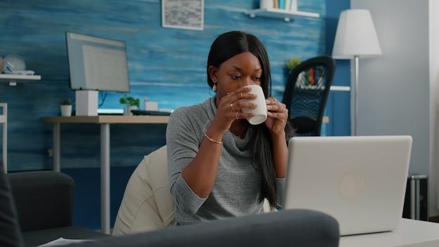 Студент улыбается во время работы над статьей в блоге в социальных сетях, набирая коммуникационный проект, сидя в гостиной