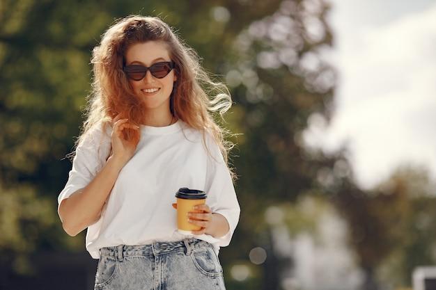 一杯のコーヒーが付いている都市に立っている学生
