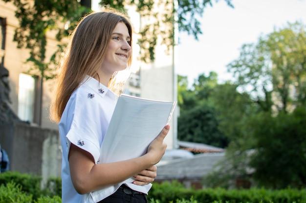 Студент стоит возле университета