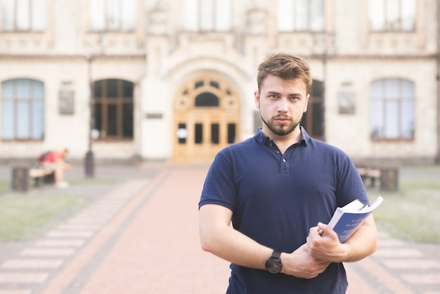 Student standing outside college building