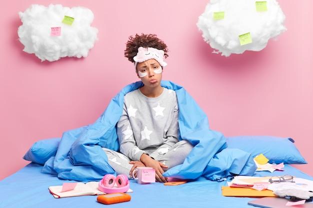 Студент учится из дома во время карантина из-за коронавируса сидит, скрестив ноги, в постели, проходит косметические процедуры, накрытый одеялом