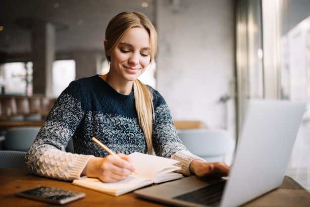 Student studying, using laptop computer, online education. beautiful woman freelancer writes notes, planning working project, working from home