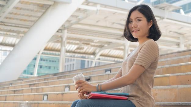 教育本とコーヒーカップを持つ学生の十代の少女は、階段の歩行者の上に座る