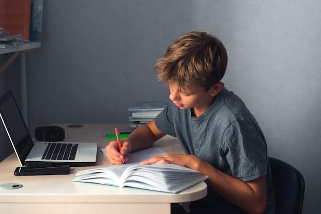 Мальчик-подросток-студент делает домашнее задание с ноутбуком и компьютером на рабочем месте дома