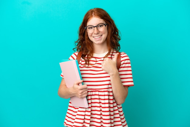 Student teenager redhead girl isolated on blue background giving a thumbs up gesture
