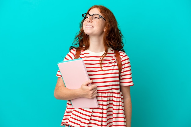 Student teenager redhead girl isolated on blue background thinking an idea while looking up