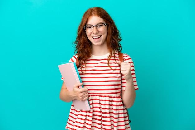 우승자 위치에서 승리를 축하하는 파란색 배경에 고립 된 학생 십 대 빨간 머리 소녀