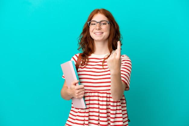 来たるジェスチャーをしている青い背景に分離された学生のティーンエイジャーの赤毛の女の子