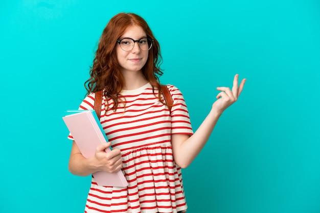 青い背景に隔離された学生のティーンエイジャーの赤毛の女の子は、来るように招待するために手を横に伸ばします