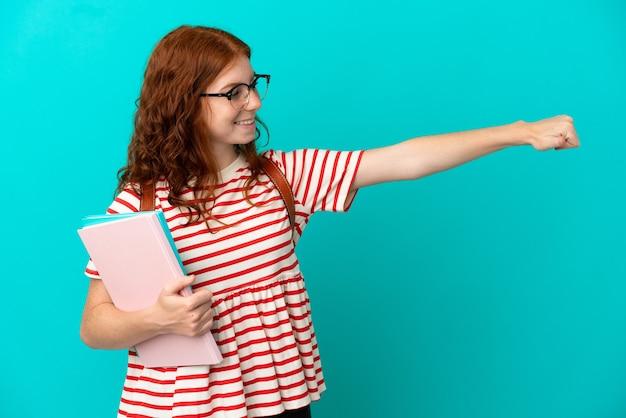 Студент подросток рыжая девушка изолирована на синем фоне, показывая палец вверх жест