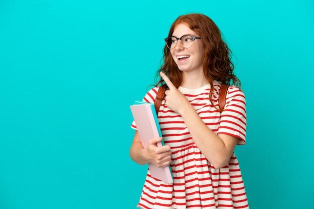 파란색 배경에 격리된 학생 10대 빨간 머리 소녀는 손가락을 들어올리면서 솔루션을 실현하려고 합니다.