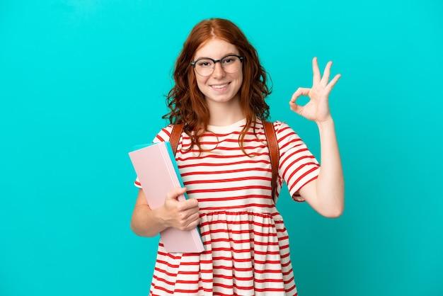Студент подросток рыжая девушка изолирована на синем фоне показывает знак ок пальцами