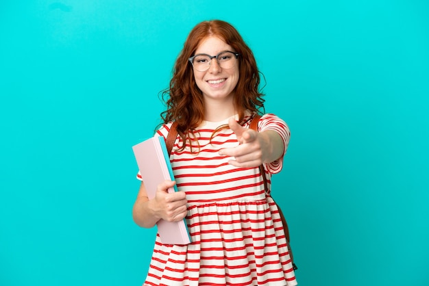 青い背景に分離された学生のティーンエイジャーの赤毛の女の子は驚いて正面を指しています