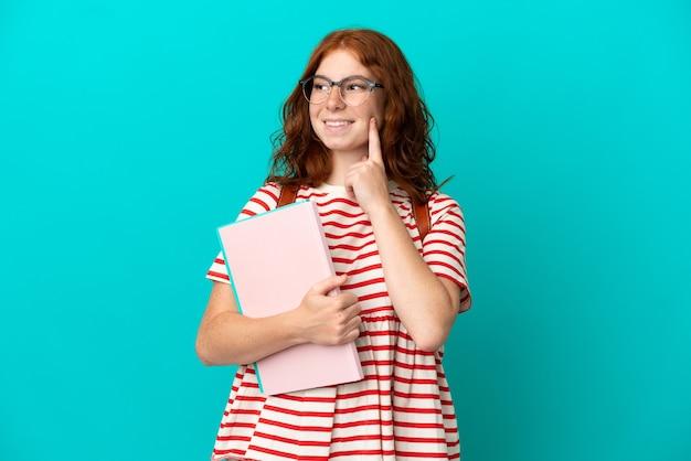 파란색 배경에 고립 된 학생 십 대 빨간 머리 소녀 찾는 동안 아이디어를 생각