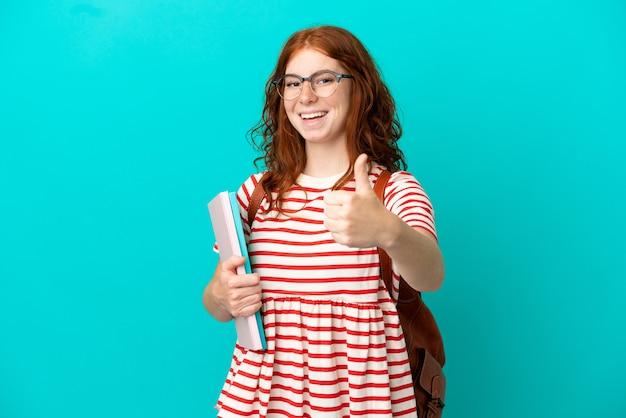 파란색 배경에 고립된 학생 10대 빨간 머리 소녀는 좋은 일이 있었기 때문에 엄지손가락을 치켜들었습니다.