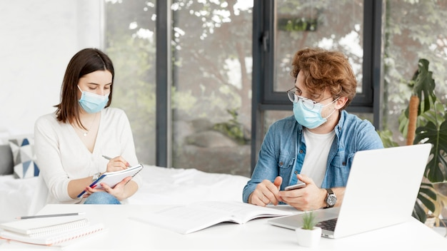 Student and tutor wearing medical masks front view