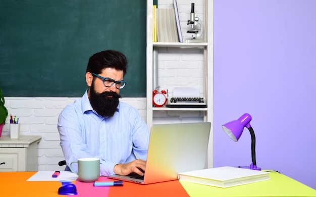 Student and tutoring education concept male student thinking about coursework in university bearded