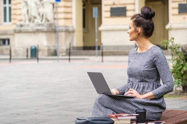 Студент использует ноутбук на скамейке