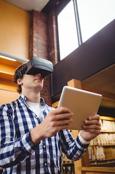Student using digital tablet and virtual reality headset in library