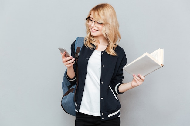 Student using phone and holding book