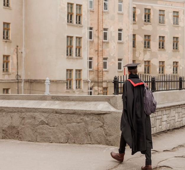 Studente che cammina alla cerimonia di laurea
