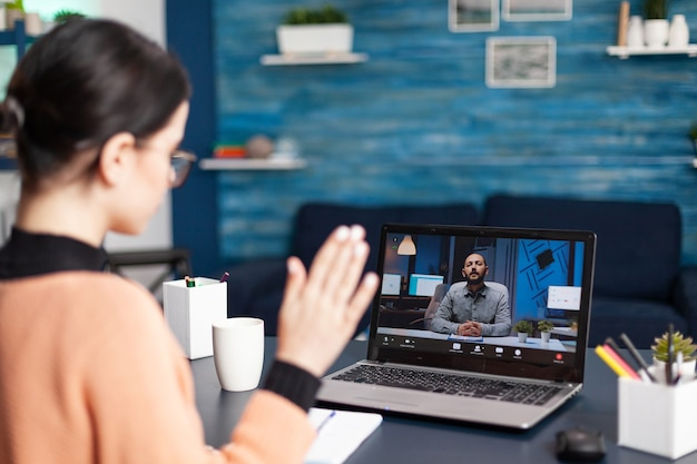 Student waving hand to her university teacher during videocall meeting. caucasian female discussing about remote education because of coronavirus quarantine while sitting at desk in living room