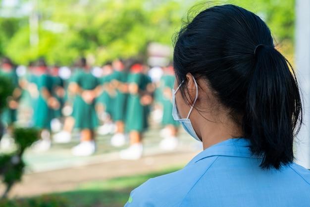 학생은 학교에 서있는 얼굴 마스크를 착용