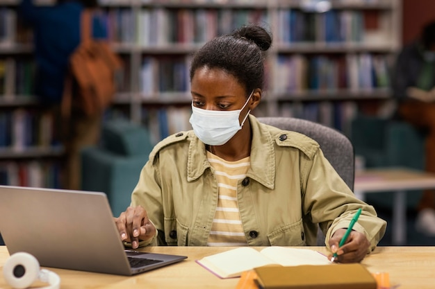 Студент в масках для лица в библиотеке