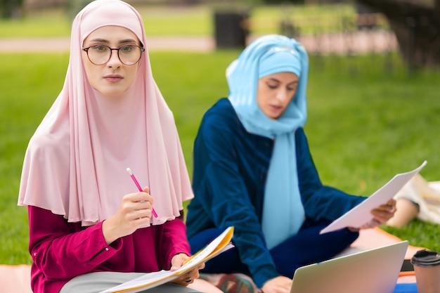 眼鏡をかけている学生。眼鏡をかけている勤勉なイスラム教徒の学生は、試験の準備中に思慮深く感じています