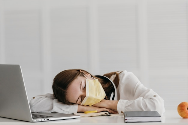Студент в медицинской маске и спит