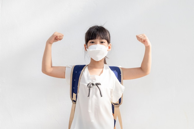 Student wearing surgical face mask and backpack