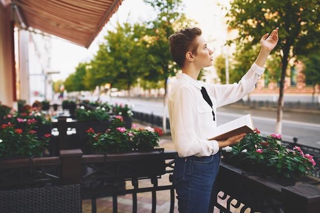 도시 여름 교육에서 거리 휴가에 그의 손에 책을 가진 학생